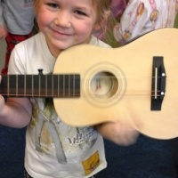 daycare in Colorado springs, image of child with a guitar.