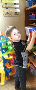 kid putting toys away