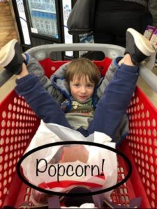child in shopping trolley with popcorn