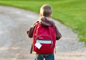 boy-in-brown-hoodie-carrying-red-backpack-while-walking-on-207697