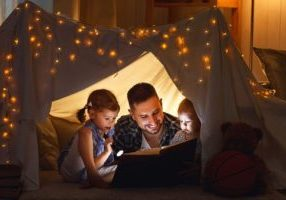 father reading with his kids under flashlight
