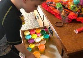 child organizing toys in drawer